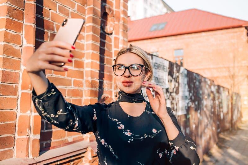 Sch?nes nettes blondes Modell im Kleid, das in der Stadt aufwirft stockbilder