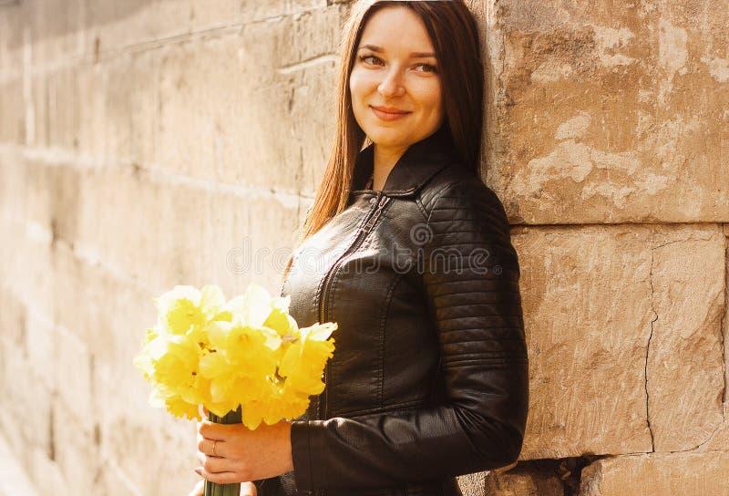 Sch?nes Portr?t der brunette Frau gelbe Fr?hlingsblumen halten lizenzfreie stockfotografie