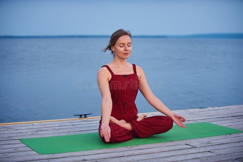 Sch?nes Praxisyoga asana Padmasana der jungen Frau - Lotus-Haltung auf der h?lzernen Plattform nahe dem See lizenzfreie stockbilder