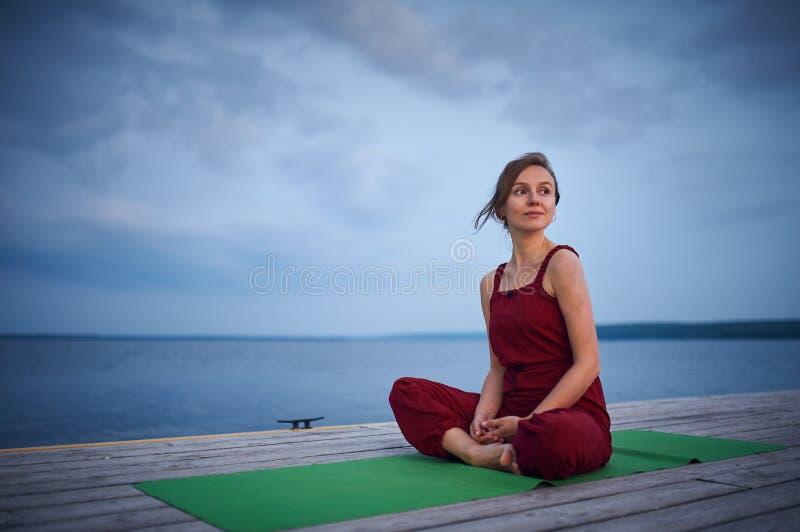 Sch?nes Praxisyoga asana Padmasana der jungen Frau - Lotus-Haltung auf der h?lzernen Plattform nahe dem See lizenzfreie stockfotos