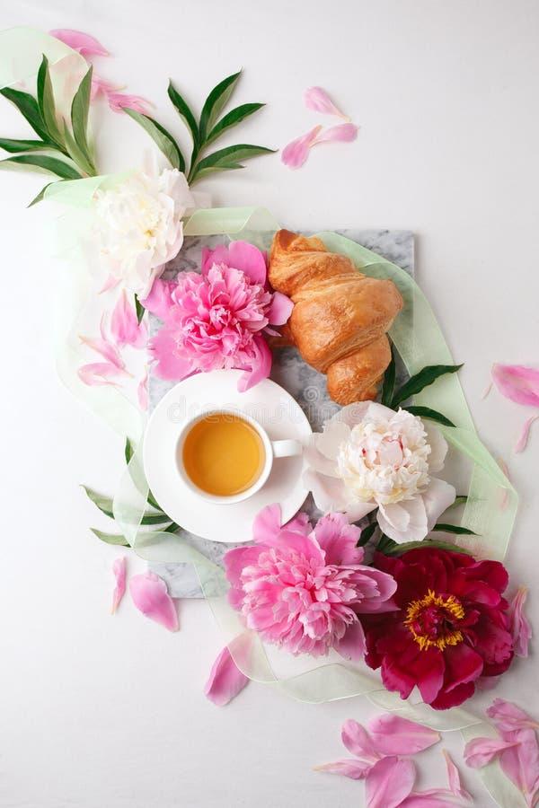 Sch?nes Stillleben mit Teeschale und Pfingstrosen Draufsicht, französisches Frühstück des Sommers vom bloger, weibliches Feiertag lizenzfreies stockfoto