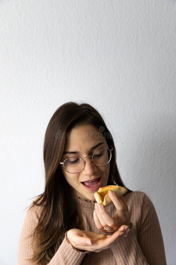 Sch?nes und gl?ckliches Frauenportr?t, das hamantash Purim-Aprikosenpl?tzchen isst stockfotos