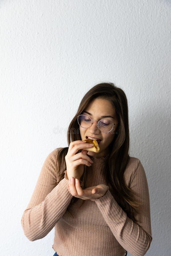 Sch?nes und gl?ckliches Frauenportr?t, das hamantash Purim-Aprikosenpl?tzchen isst lizenzfreies stockfoto