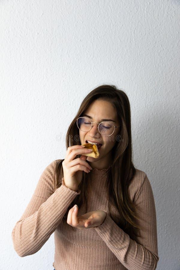 Sch?nes und gl?ckliches Frauenportr?t, das hamantash Purim-Aprikosenpl?tzchen isst lizenzfreie stockfotos