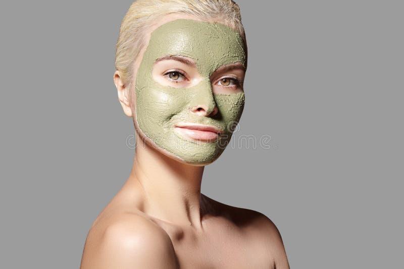 Sch?nheit, die gr?ne Gesichtsmaske anwendet Sch?nheits-Behandlungen Badekurort-M?dchen wenden Clay Facial-Maske auf grauem Hinter lizenzfreie stockfotografie