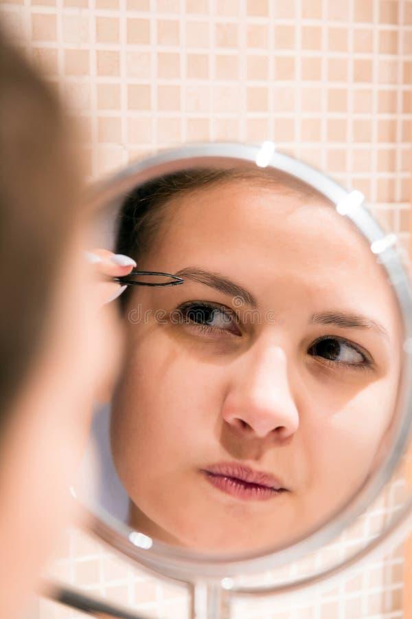 Sch?nheit mit Pinzette zupft Augenbrauen beim Untersuchung den Spiegel im Badezimmer Sch?nheit skincare und Wellnessmorgen stockfotografie