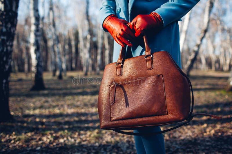 Sch?nheit und Mode Stilvolle moderne Frau, die das helle Kleid h?lt braune Taschenhandtasche tr?gt lizenzfreies stockbild
