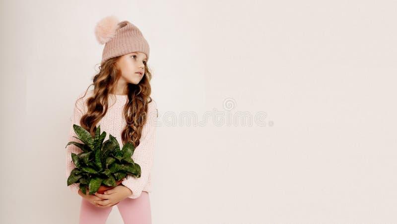 Sch?nheit und Modekonzept: Kleines M?dchen, das rosa Ausstattung tr?gt und vollen K?rper der Blume h?lt lizenzfreies stockbild