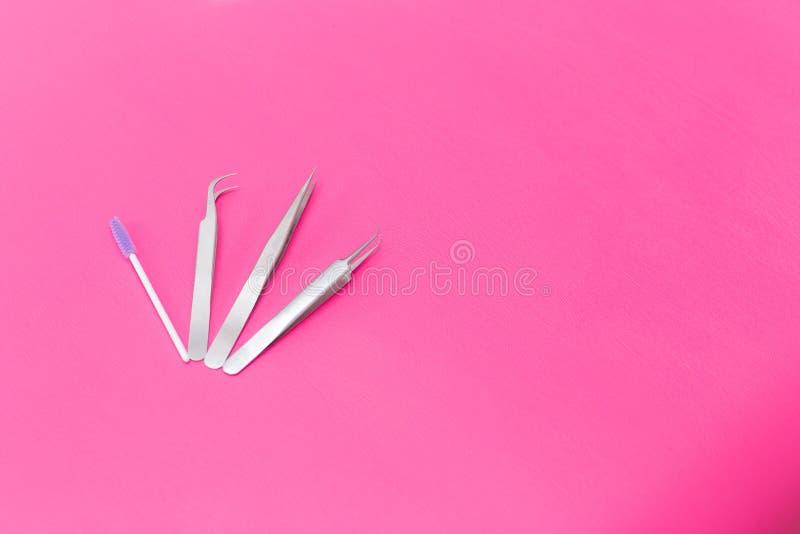 Sch?nheit und Modekonzept - Werkzeuge f?r Wimper-Erweiterungs-Verfahren Pinzette auf rosa Hintergrund copyspace Modell stockfotografie