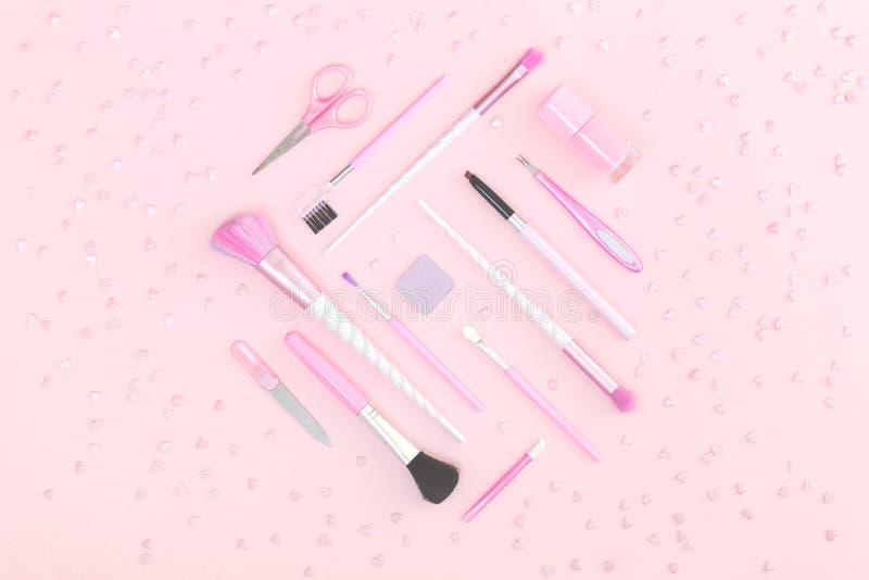 Sch?nheitseinhorn-Make-upb?rsten auf silbernem Rosa stockfoto