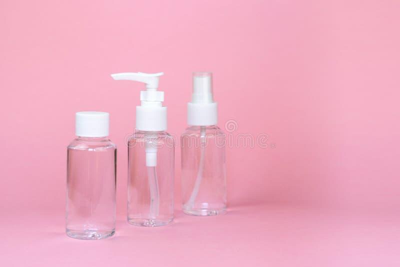 Sch?nheitskosmetik glassbottle; einbrennender Spott oben; Vorderansicht ?ber rosa Pastellhintergrund stockbilder