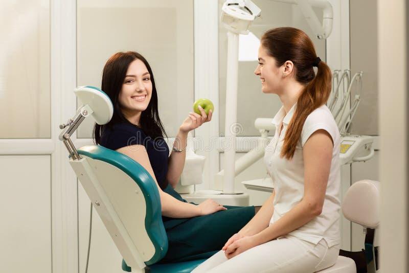 Sch?nheitspatient, der zahnmedizinische Behandlung in Zahnarzt ` s B?ro hat Lächelnde Frau hält einen Apfel stockfoto