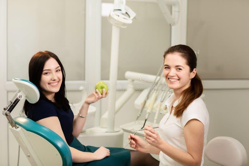 Sch?nheitspatient, der zahnmedizinische Behandlung in Zahnarzt ` s B?ro hat L?chelnde Frau h?lt einen Apfel stockbilder