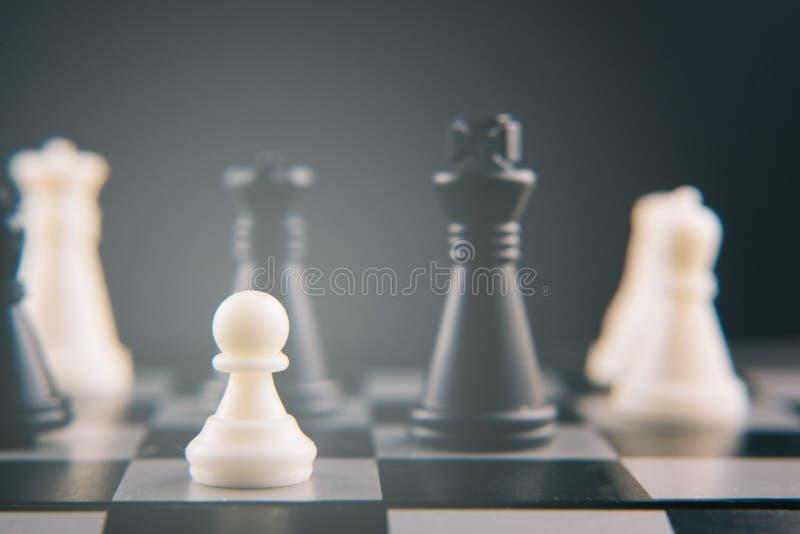 Schaak op schaakraad die wordt geplaatst pand tegen anderen stukken macht, slaven en arbeidersconcept stock afbeelding