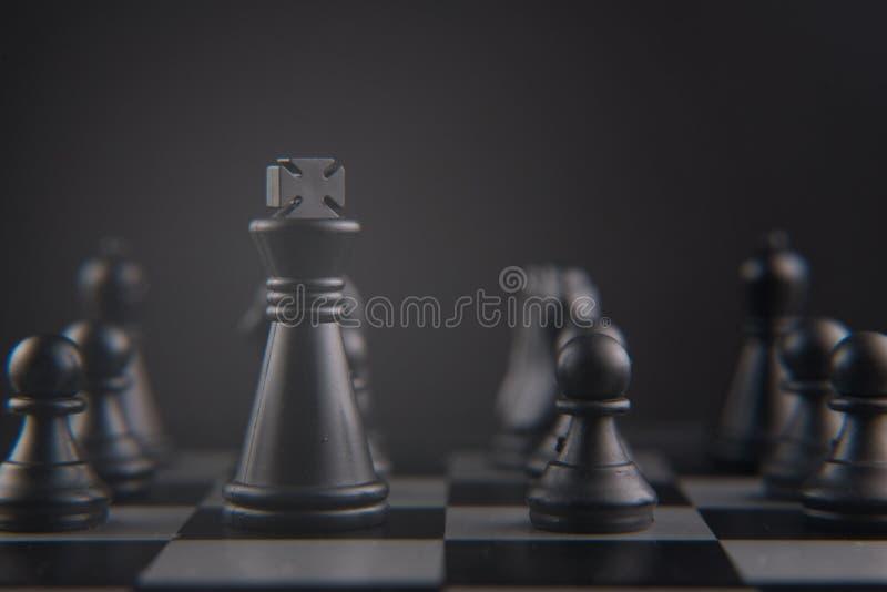 Schaak op schaakraad die wordt geplaatst zwarte koning en pandstukken leider, strategie en groepswerkconcept stock foto's