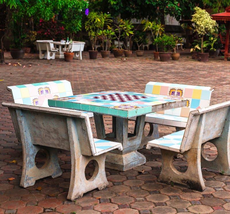 Schaak, schaakbordlijst en banken in openbaar park stock afbeeldingen