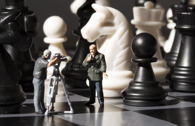Schaaknieuws het maken Het spelproces van het filmschaak Miniatuurjournalisten op schaakbord stock fotografie