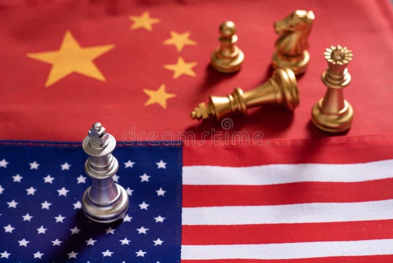 Schaakspel, ??n koningstribune als winnaar over andere op de nationale vlaggen van China en van de V.S. Het Concept van de handel stock fotografie
