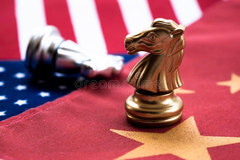 Schaakspel, twee ridders face to face op China en de nationale vlaggen van de V.S. Het Concept van de handelsoorlog Conflict tuss stock foto