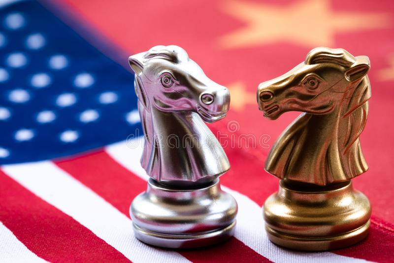 Schaakspel, twee ridders face to face op China en de nationale vlaggen van de V.S. Het Concept van de handelsoorlog Conflict tuss stock foto's