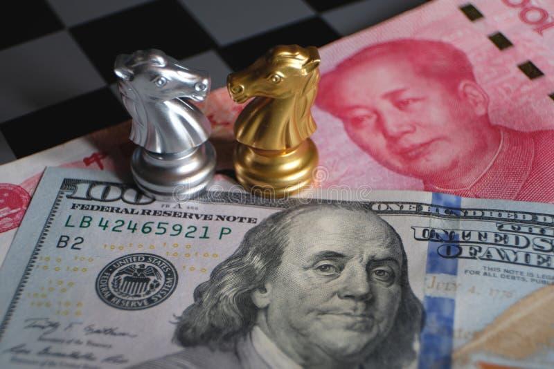 Schaakspel, twee ridders face to face op Chinese yuans en Amerikaanse dollarachtergrond Het concept van de handelsmanier Conflict stock foto's