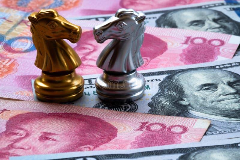 Schaakspel, twee ridders face to face op Chinese yuans en Amerikaanse dollarachtergrond Het Concept van de handelsoorlog Conflict stock foto