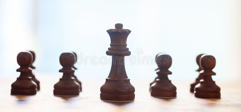 Schaakstukken donkere bruine kleur Sluit omhoog mening van koningin en panden met details Vage achtergrond royalty-vrije stock foto's