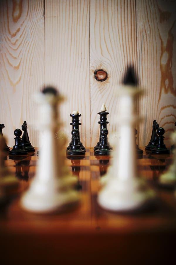 Schaakstukken op een schaakbord Zwarte koning en koningin voor wit stock foto's