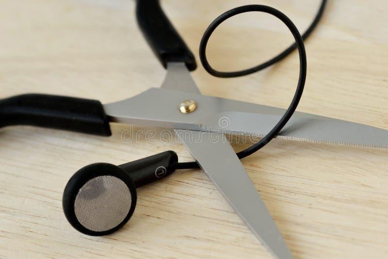 Schaar die de draad van hoofdtelefoons snijden - oortelefoons Concept het luisteren en mededeling, draadloze hoofdtelefoons stock afbeelding
