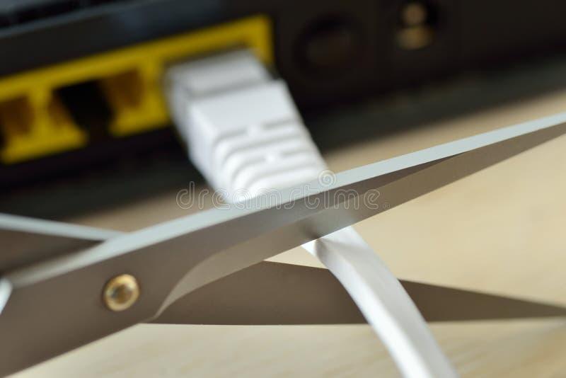 Schaar die Internet-de kabel van de modemrouter snijden - Concept netwerk en gegevensbescherming stock fotografie