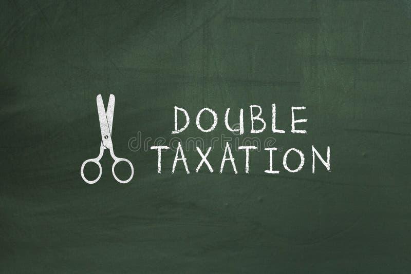 Schaar en Dubbele belastingheffingstekst op bord stock fotografie