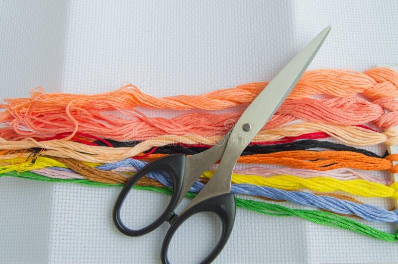 Schaar en heldere kleurrijke draad voor borduurwerkdraad op canvas Met de hand gemaakte toebehoren op witte achtergrond Plaats vo royalty-vrije stock afbeelding