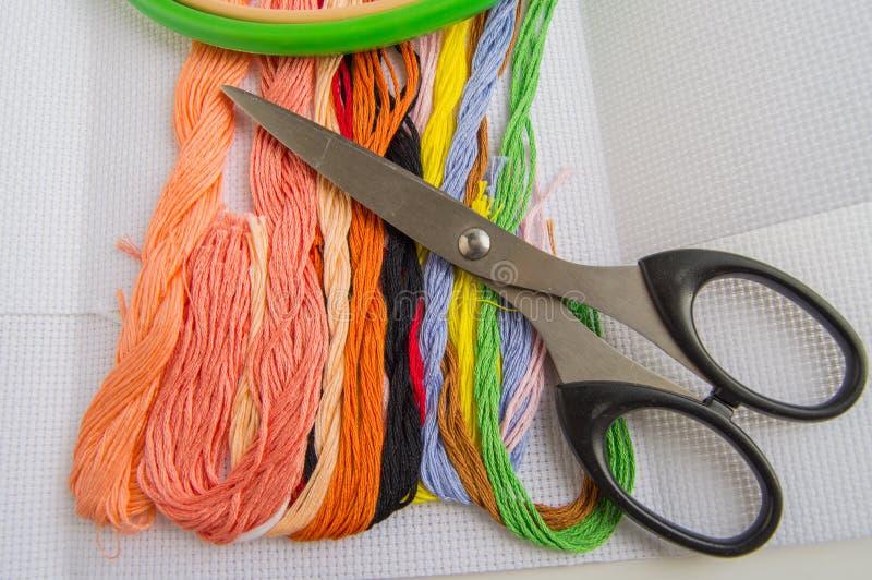 Schaar en heldere kleurrijke draad voor borduurwerkdraad op canvas Met de hand gemaakte toebehoren op witte achtergrond Plaats vo royalty-vrije stock afbeeldingen
