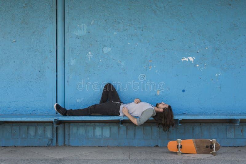Schaatser die op blauwe achtergrond met een oranje skateboard dichtbij hem liggen royalty-vrije stock fotografie