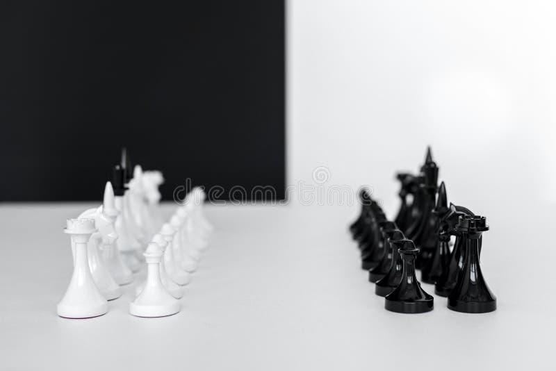 Schach erscheint in den Reihen auf weißer Tischplatte nahe Schwarzweiss-Wand stockbild