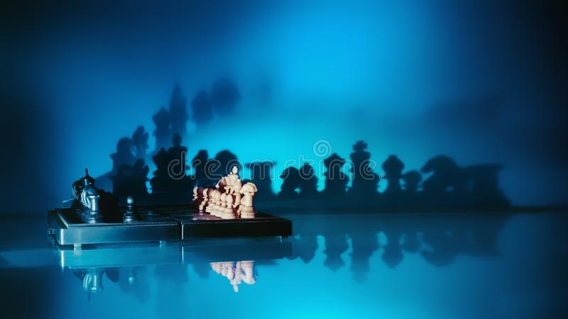 Schach mit dunklen Schatten auf einem blauen Hintergrund stockfotografie