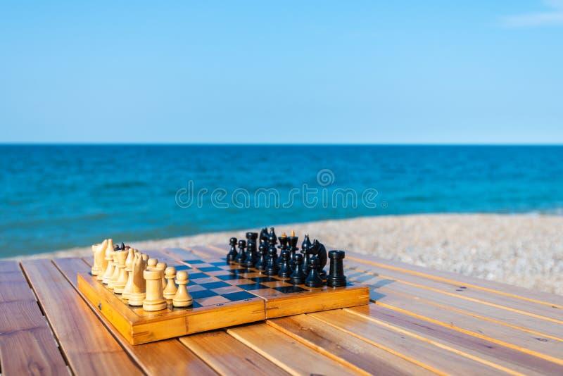 Schachbrett auf dem Tisch durch das Meer stockfoto