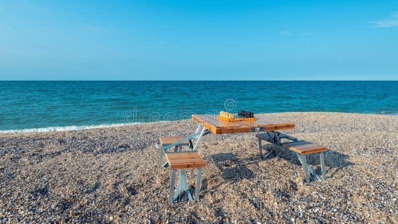 Schachbrett auf dem Tisch durch das Meer lizenzfreie stockfotos
