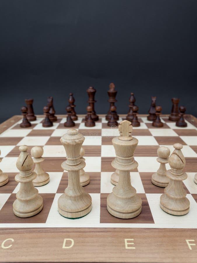 Schachbrett mit hölzernen Zahlen setzte gegenüber von einander stockbilder