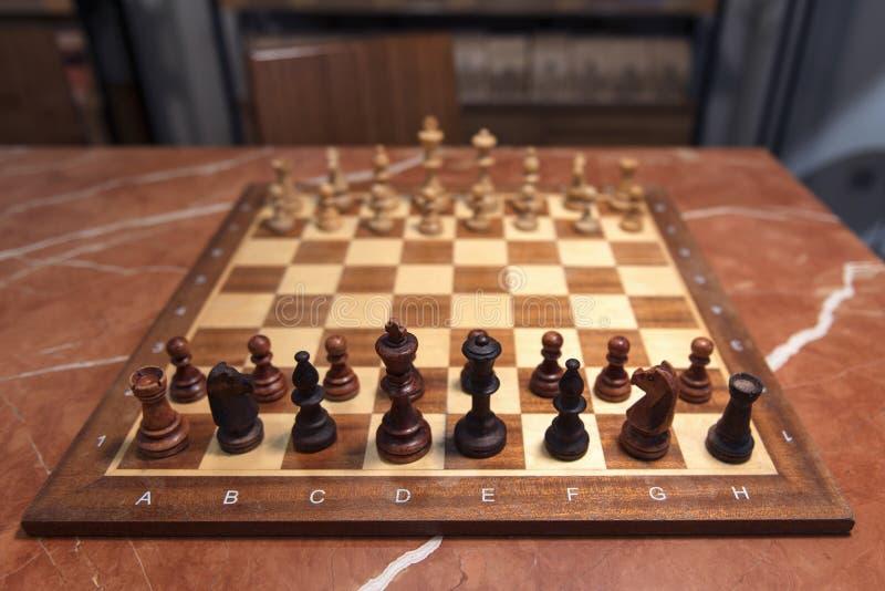 Schachbrett mit Zahlen auf brauner Marmortabelle Anfang des Spiels lizenzfreies stockfoto