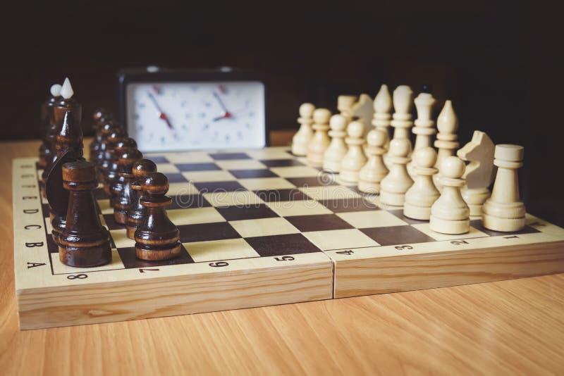Schachbrett, Schachfiguren und Schachuhrnahaufnahme Im Bild gibt es einen König, eine Königin und einen Saatkrähe Der Anfang des  lizenzfreies stockbild