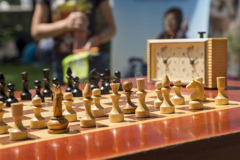 Schackbräde med stycken och klocka på träskrivbordet i anslutning med schackturneringen fotografering för bildbyråer