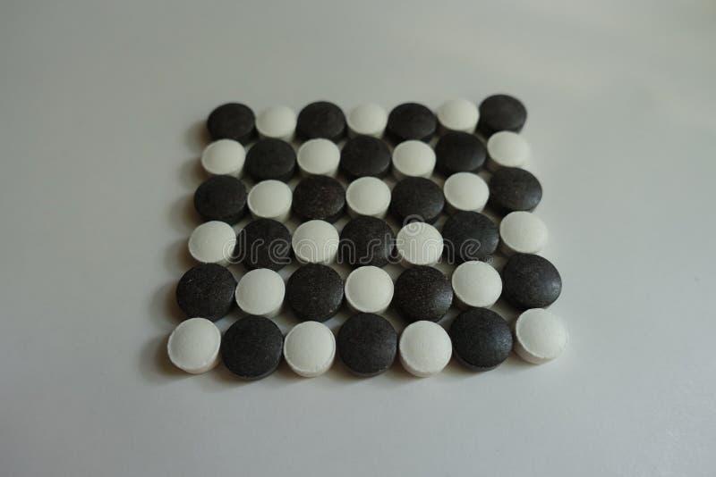 Schackbrädemodell som göras av svartvita piller arkivfoton
