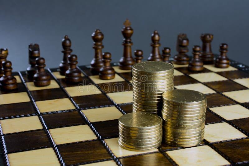 Schackbrädet figurerar högar av guld- mynt arkivbilder