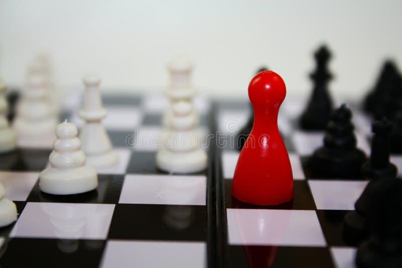 Schacklek med den ljusa röda statyetten för fia på schackbrädet med andra schackstycken royaltyfria bilder