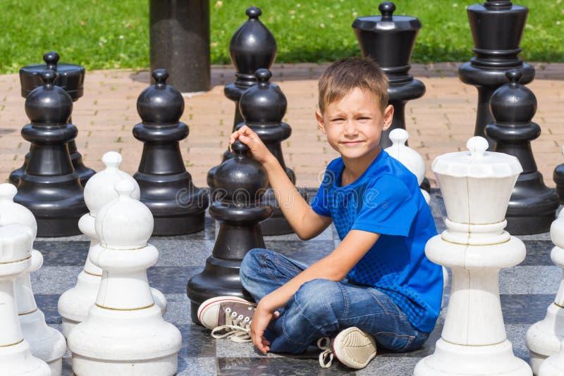 Schacklek med det jätte- schackstycket Pojke som placerar och spelar den strategiska utomhus- leken på svartvitt bräde arkivfoto