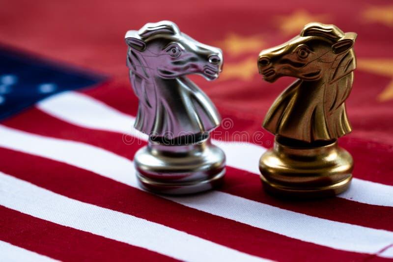 Schackleken, två riddare vänder mot - - framsidan på Kina och USA-nationsflaggor Begrepp f?r handelkrig Konflikt mellan två stora royaltyfri bild