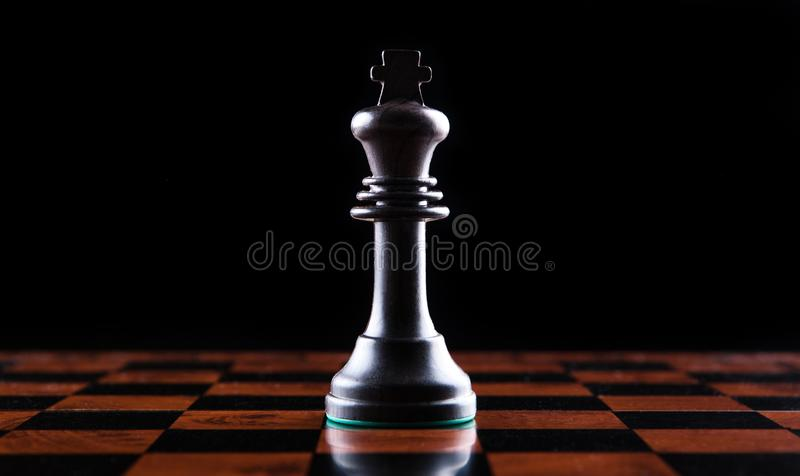Schackstycke av en svart konung på en schackbräde på en svart backgroun arkivfoton