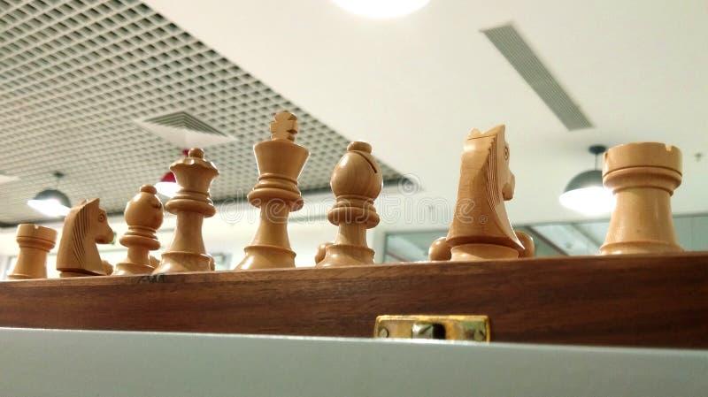 Schackstycke på schackbräde med takgarneringbakgrund arkivfoton