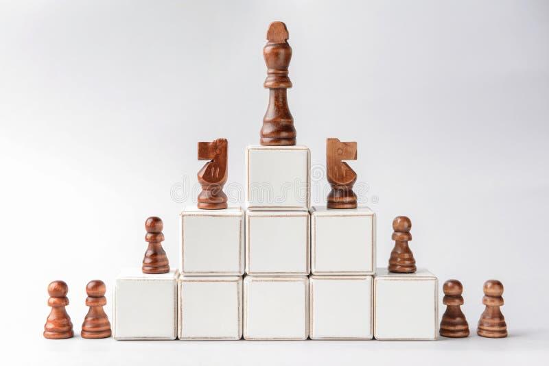 Schackstycken med kuber på ljus bakgrund royaltyfri foto